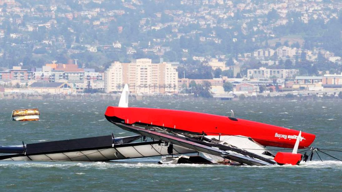 The Artemis Racing yacht is towed to shore after capsizing in the San Francisco Bay