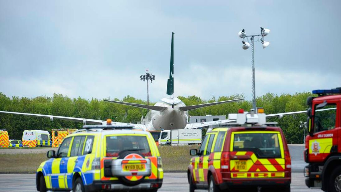 A Pakistan International Airlines is surrounded by emergency vehicles on the tarmac at Stansted Airport