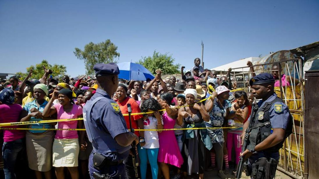 South African police stand guard as residents of Diepsloot gather where two toddlers were found dead