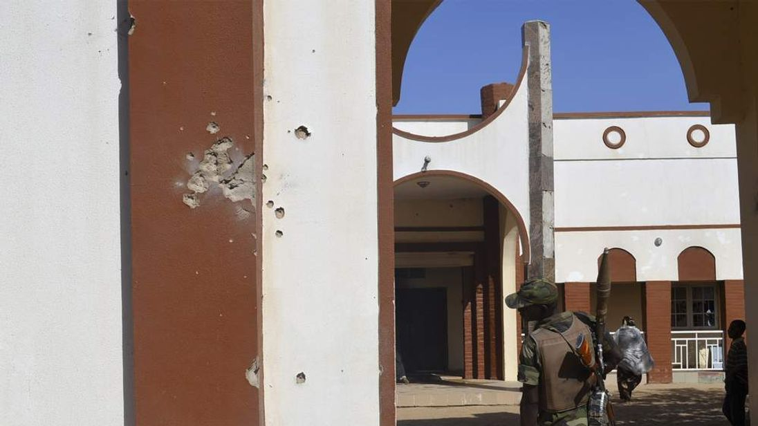 A soldier examines a wall riddled with bullets, from an attack by Boko Haram Militants