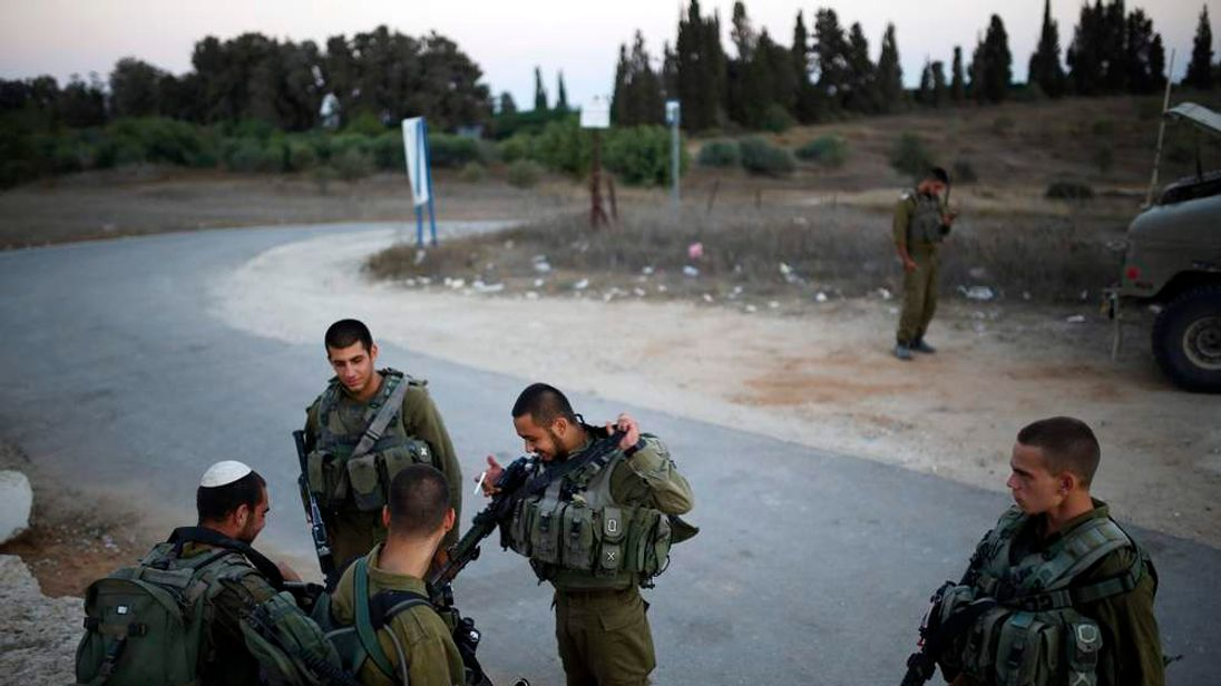 Israeli soldiers rest just outside the border with the northern Gaza Strip