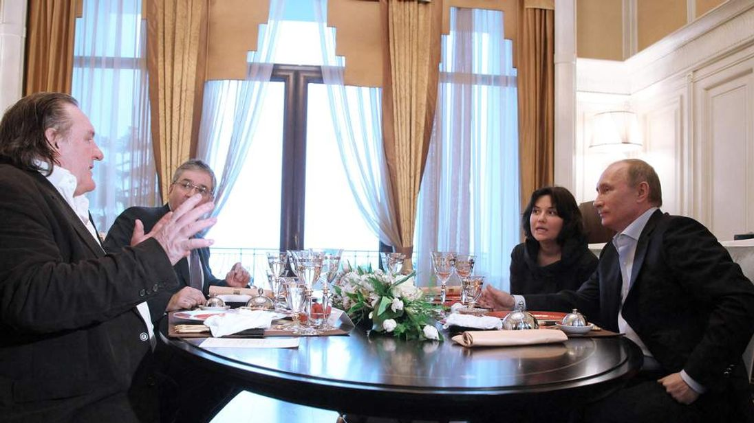 French actor Gerard Depardieu, left, speaks to President Vladimir Putin and unidentified aides