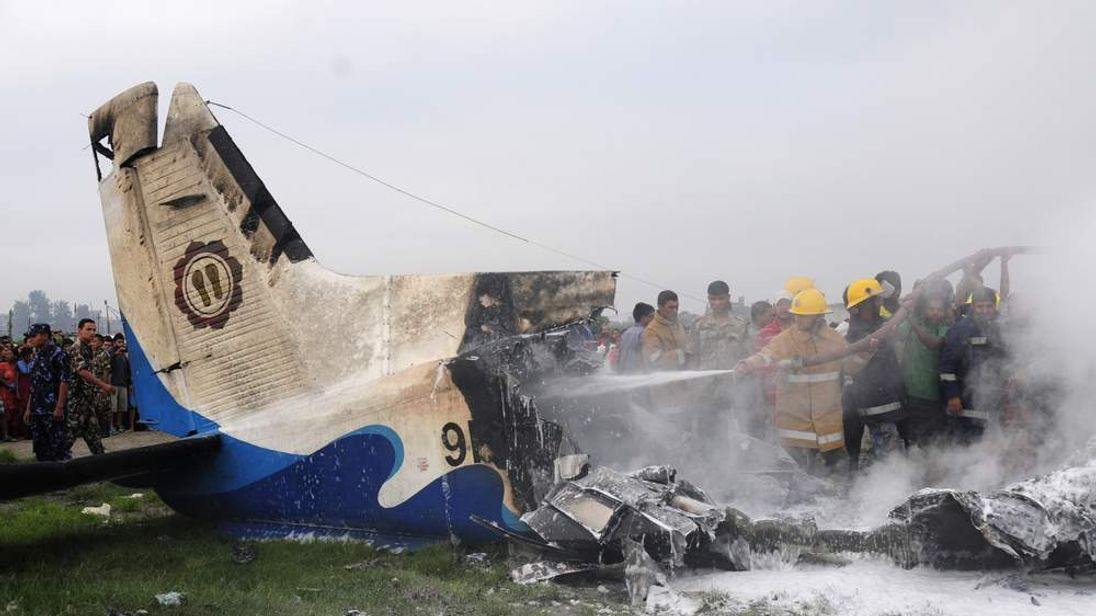 Nepalese fireman and volunteers help extinguish flames from the wreckage of the Sita airplane