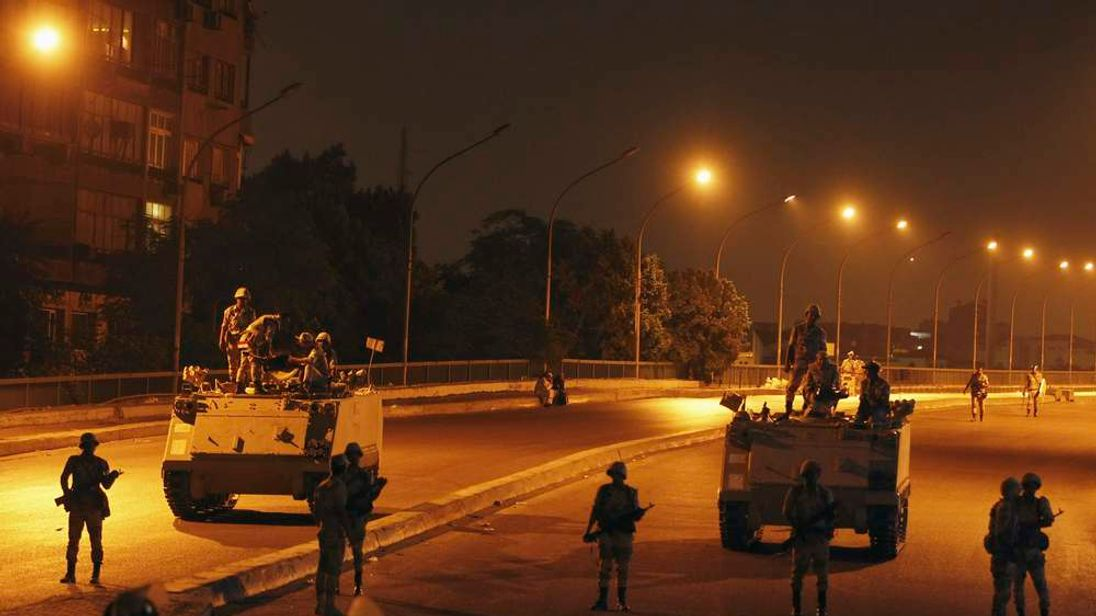 Army soldiers take their positions on the bridge towards members of the Muslim Brotherhood and supporters of Mursi standing guard around Cairo University and Nahdet Misr Square in Giza, on the outskirts of Cairo