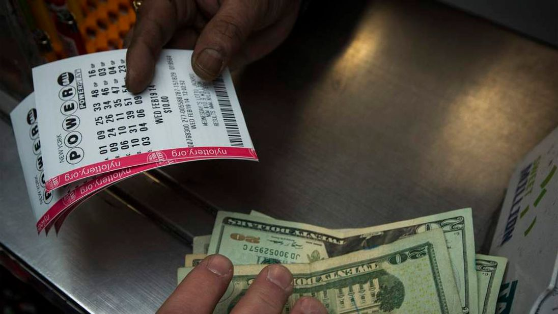 A man purchases New York State Lottery tickets for the $400 million Powerball lottery in New York's financial district