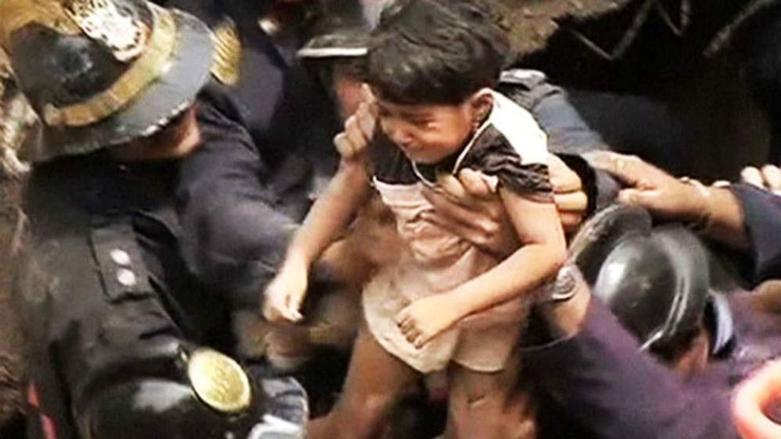 A toddler is puled out alive from the rubble of a collapsed building in Mumbai