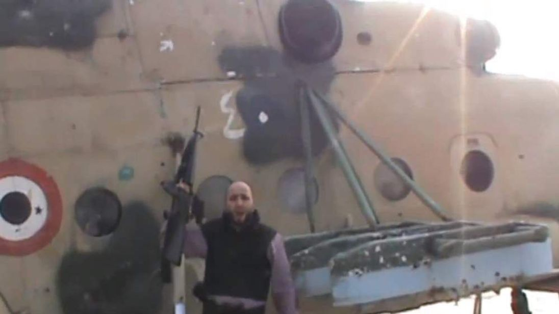 A rebel fighter beside a helicopter gunship at Marj al-Sultan airport
