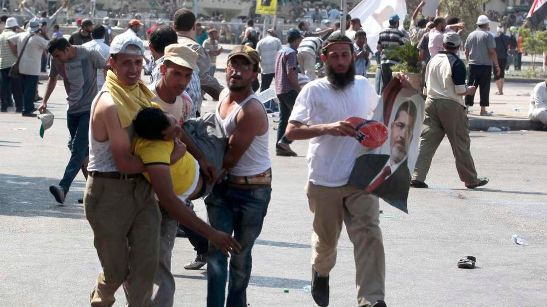 An injured man is carried during clashes outside the Republican Guard building in Cairo