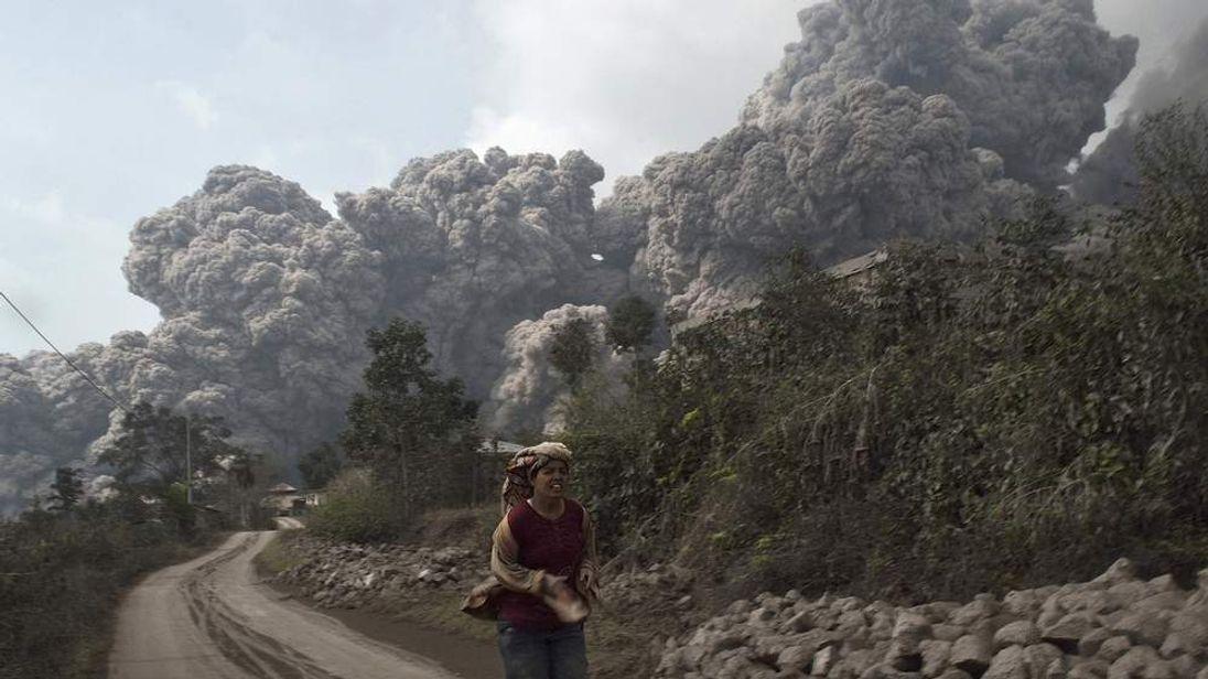 A villager run as Mount Sinabung erupt at Sigarang-Garang village in Karo district, Indonesia
