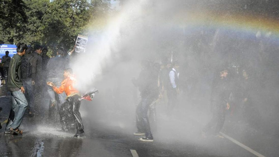 An Indian protester is hit by a water canon during a demonstration against the gang-rape of a student
