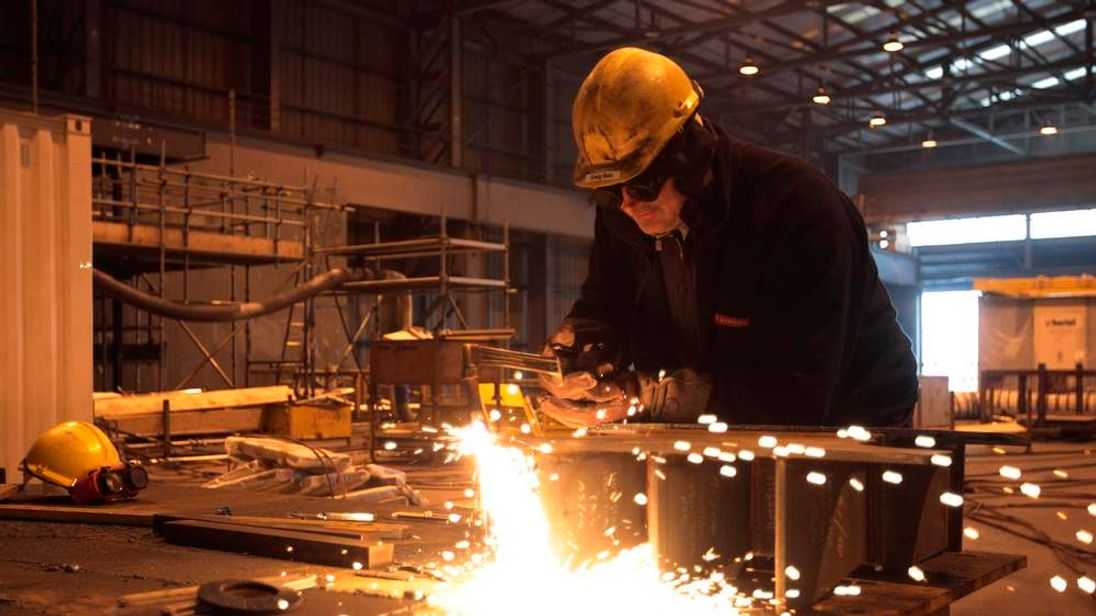 A welder works on a Queen Elizabeth Class aircraft carrier at BAE Systems Govan yard in Glasgow