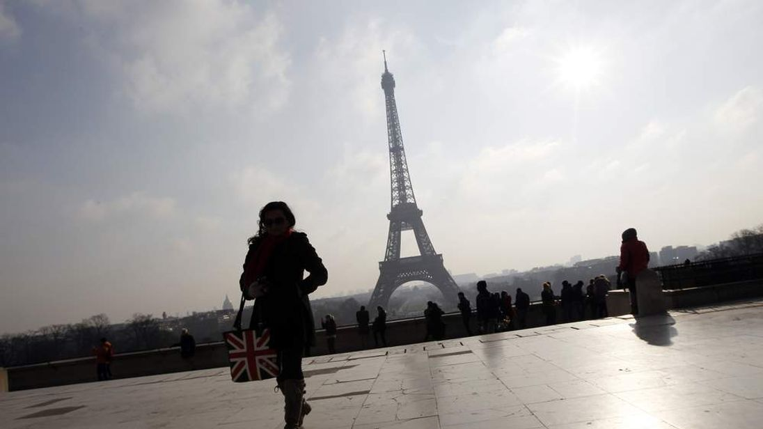 A woman walks on the Trocadero near the Eiffel Tower