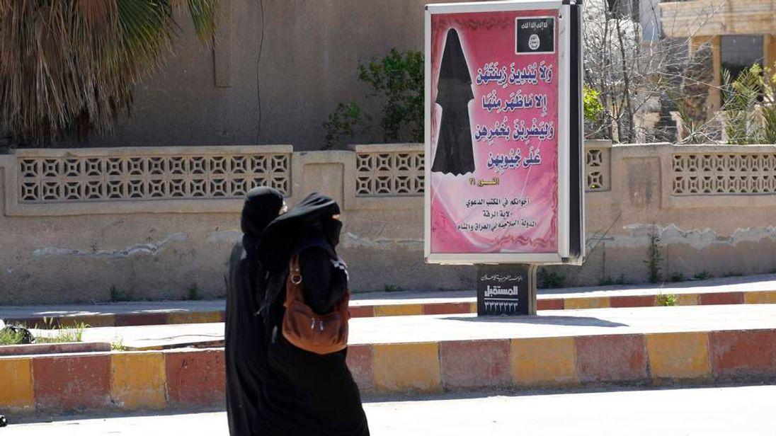 Women in Syria walk past a billboard that urges females to wear a hijab