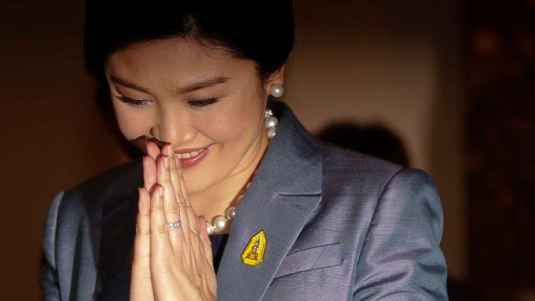 Thailand's Prime Minister Yingluck Shinawatra gives a traditional greeting as she arrives at the Constitutional Court in Bangkok