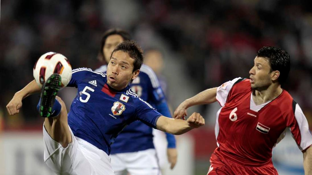 Japan's Nagatomo fights for the ball with Syria's Hussien during their 2011 Asian Cup Group B soccer match in Doha