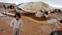 Syrian refugees stand outside their tents after heavy rain at the Al-Zaatari refugee camp in the Jordanian city of Mafraq