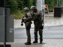 Heavily armed police officers with weapons prepare to respond to a shooting