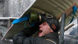 A pro-European protester reacts while taking cover during clashes with riot police in Kiev