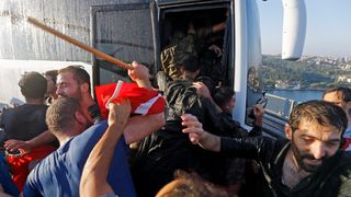 Soldiers push each other to board a bus to escape the mob after troops involved in the coup surrendered on the Bosphorus Bridge in Istanbul.