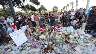 People gather around a makeshift memorial to pay tribute to the victims of an attack in the French Riviera city of Nice.
