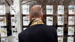 A man looks at an estate agent window