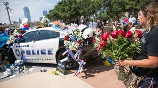 People lay flowers as a tribute to the police officers killed on Thursday night