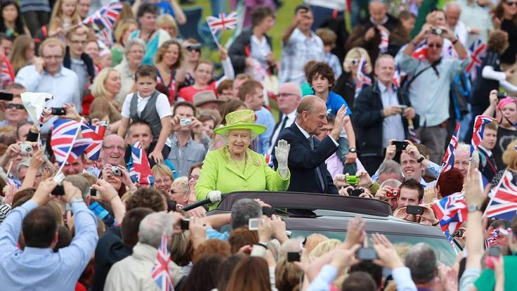 Britain's Queen Elizabeth II (Centre L) and Prince Phillip drive in a open top car as they attended a Diamond Jubilee event in the grounds of the Stormont Estate in Belfast, Northern Ireland, on June 27,