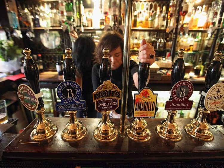 A barmaid pulls a pint in a pub