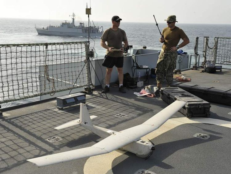 Two US Navy personnel operate a Puma - AE drone onboard the UK's Royal Fleet Auxillary Cardigan Bay, while HMS Shoreham patrols nearby