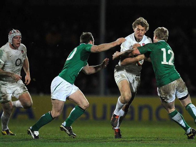 Billy Twelvetrees of England is tackled by Ian Keatley and Nevin Spence of Ireland