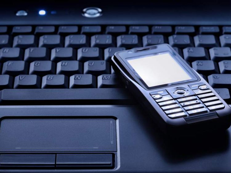 Generic phone hacking image - mobile phone sits on laptop