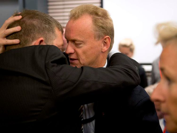Labour Party secretary Raymond Johansen, centre, hugs a relative of a Utoya massacre victim.