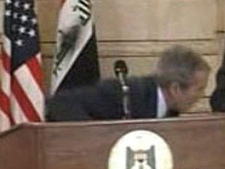 Bush takes cover from flying shoe thrown by journalist