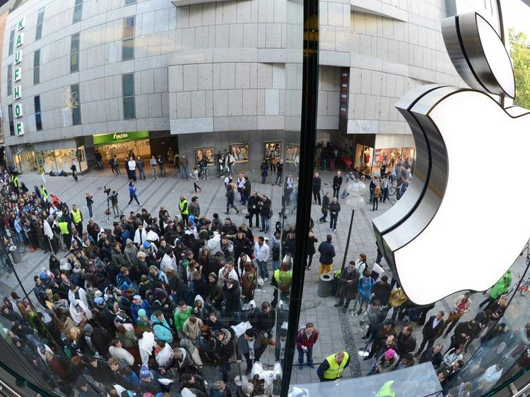 Customers queue to enter the Apple Store where a giant logo is displayed in the southern German city of Munich