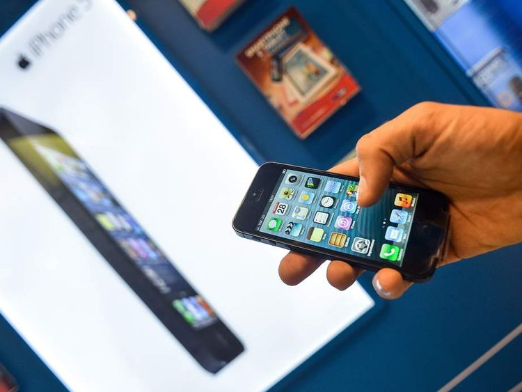 A customer holds the new Apple iPhone 5 smartphone in a telephone operator's shop in central Rome, on September 28, 2012.