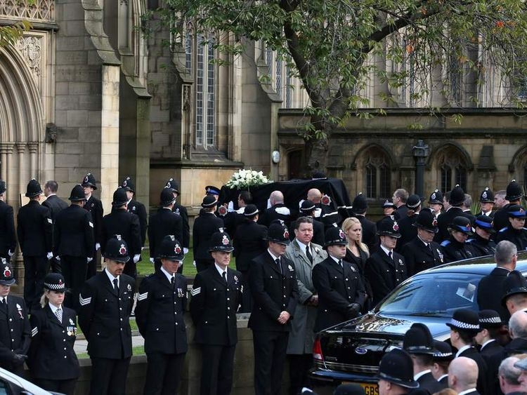 Pallbearers carry the coffin into the cathedral as police officers line the street during the funeral of police Constable Nicola Hughes