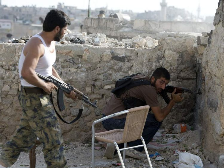 Syrian rebels take cover during clashes in the old city of Aleppo, close to the souk or bazaar district