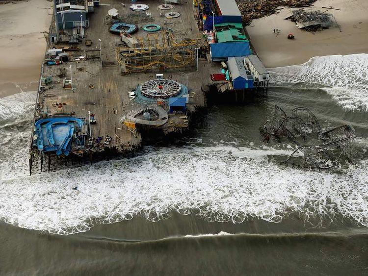 Waves break in front of a destroyed amusement park wrecked by Superstorm Sandy in Seaside Heights