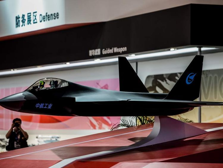 A man takes a picture of a model of a stealth plane from China Aerospace Science and Industry Corporation
