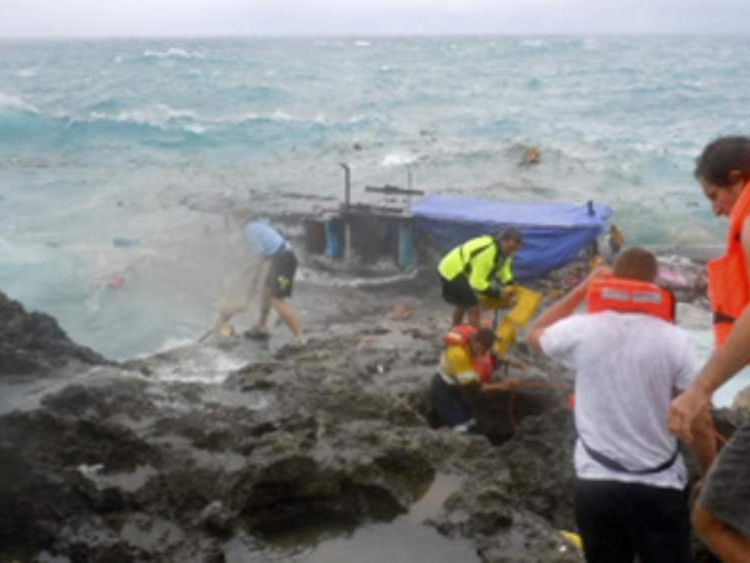 Rescuers try to reach the passengers on the people smuggler's boat