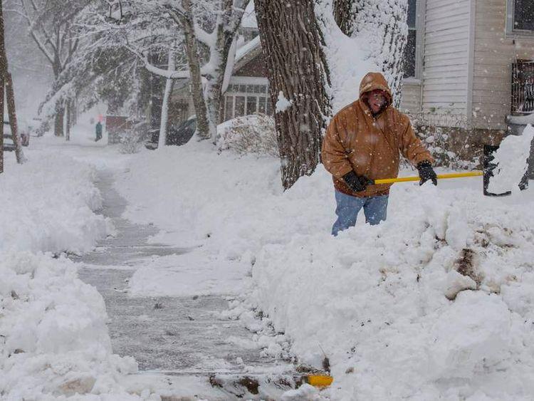 Lisa Schultz shovels her sidewalk during a winter storm in Baraboo, Wisconsin