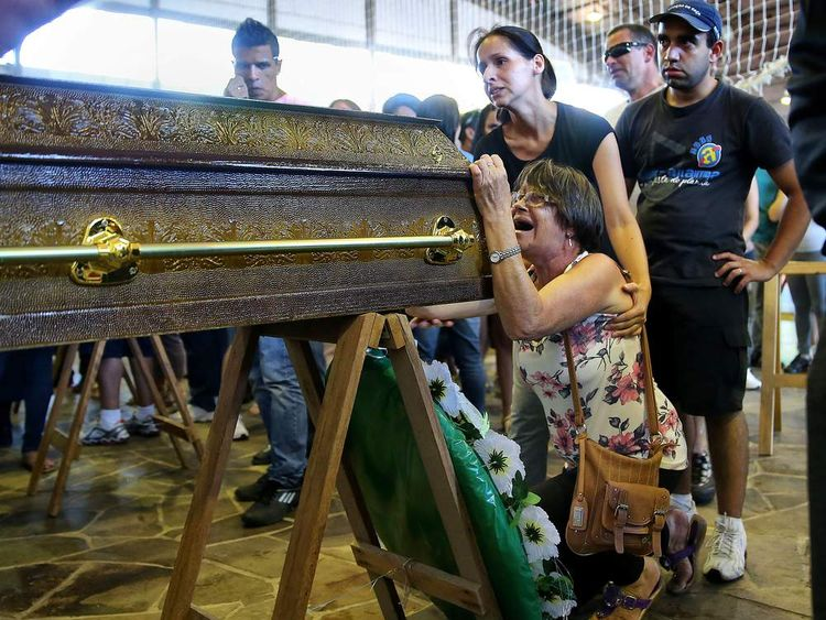 Relatives of victims from a fire that broke out at a nightclub weep, during their funeral in Santa Maria, 550 Km from Porto Alegre, southern Brazil on January 27, 2013. At least 232 people died and 131 were injured early Sunday when a fire tore through a nightclub packed with university students in the southern Brazilian city of Santa Maria, police said. AFP PHOTO / Jefferson BERNARDES (Photo credit should read JEFFERSON BERNARDES/AFP/Getty Images)