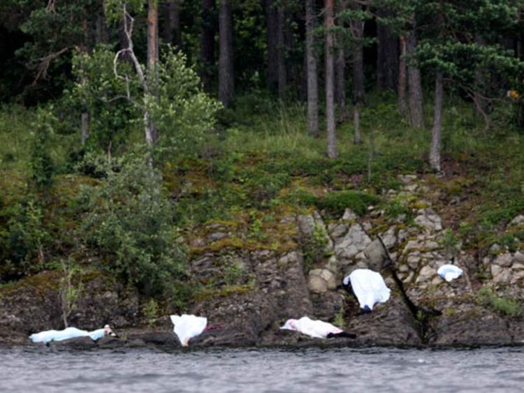 Covered corpses are seen on the shore of Utoya following shootings.