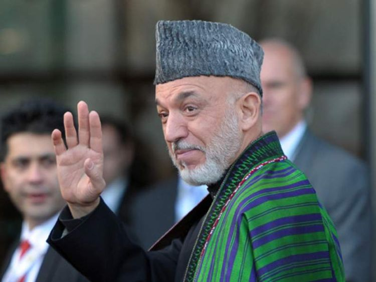 Afghan President Hamid Karzai (C) waves as he arrives to give a speech during the Afghanistan Conference