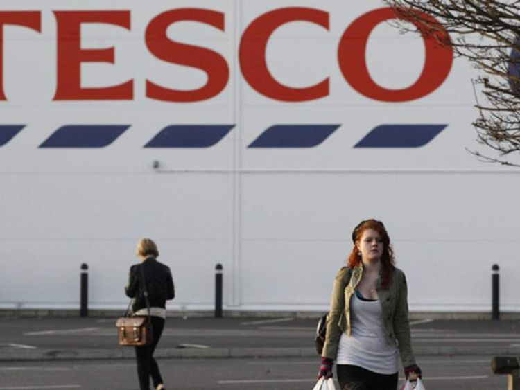 A shopper leaves a Tesco store in Loughborough, central England