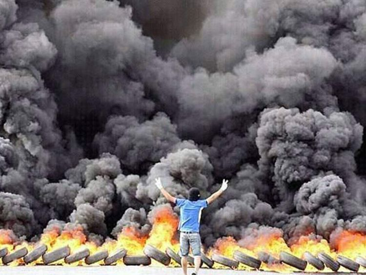 Bahraini activists took photos of themselves in front of a wall of tyres on fire as they protest the grand prix race