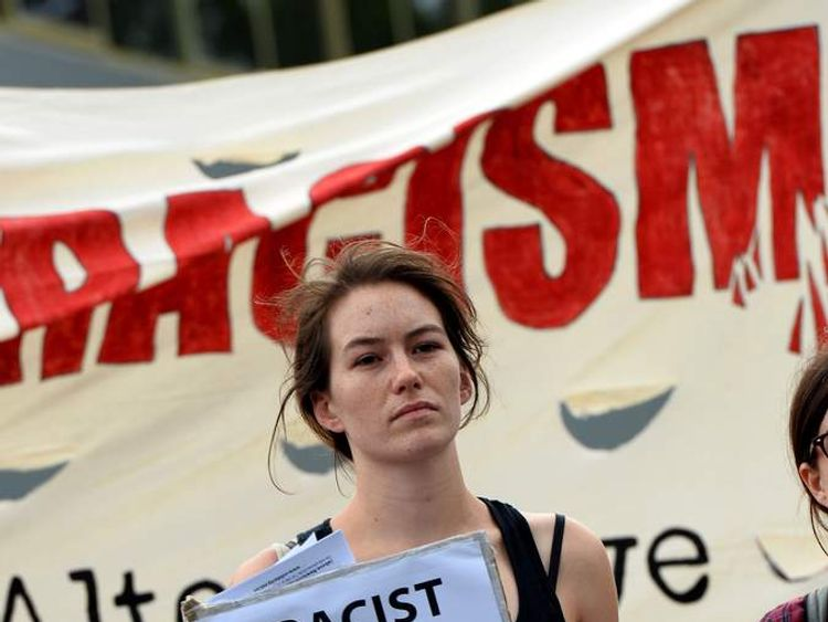 A protester holds a placard outside a venue where right-wing Dutch MP Geert Wilders delivers a speech in Sydney