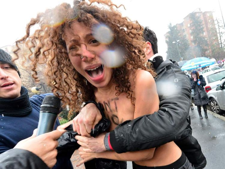 A topless feminist is arrested by riot police outside the polling station where Berlusconi went to cast his vote