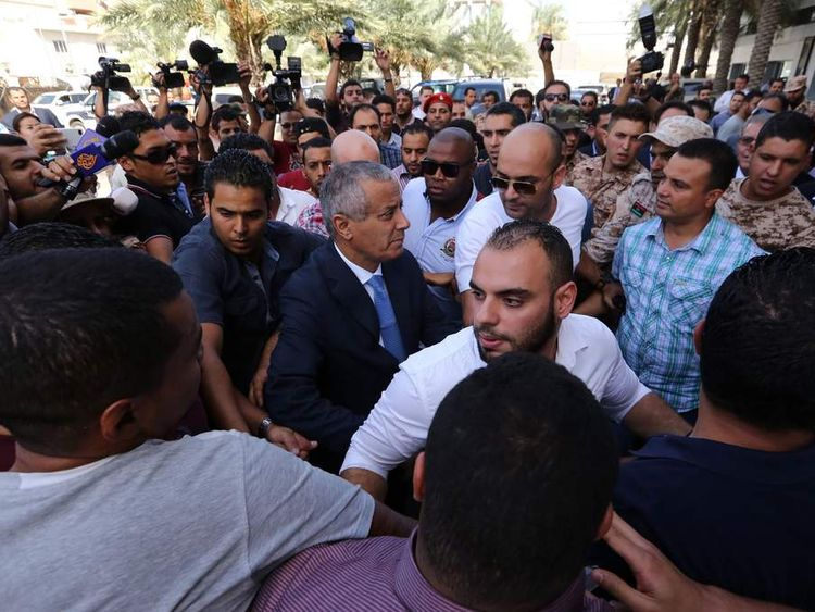 Libyan Prime Minister Ali Zeidan (C) arrives at the government headquarters in Tripoli on October 10, 2013 shortly after he was freed from the captivity of militiamen