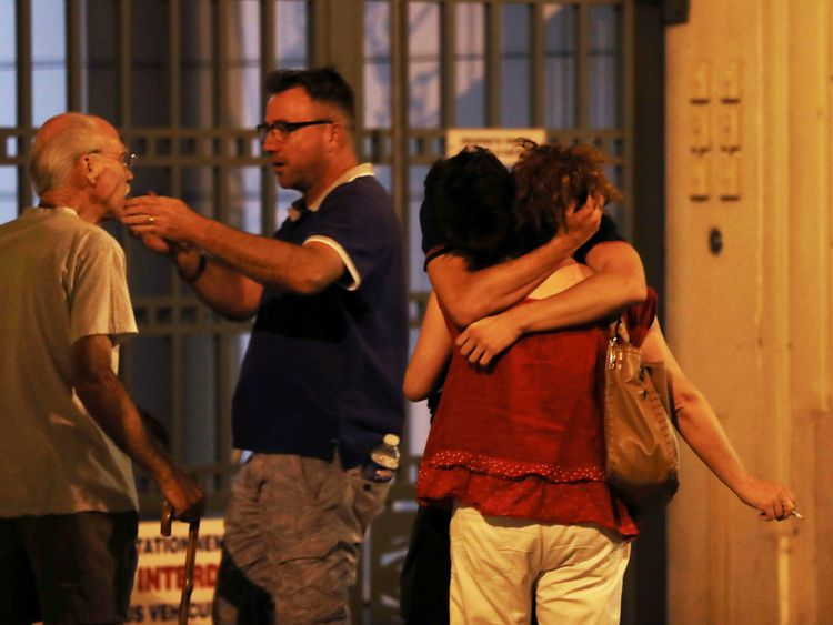 People react in the French Riviera town of Nice on July 15, 2016, after a van drove into a crowd watching a fireworks display. At least 60 people were killed when a truck ploughed into a crowd watching a Bastille Day fireworks display in the southern French resort of Nice,